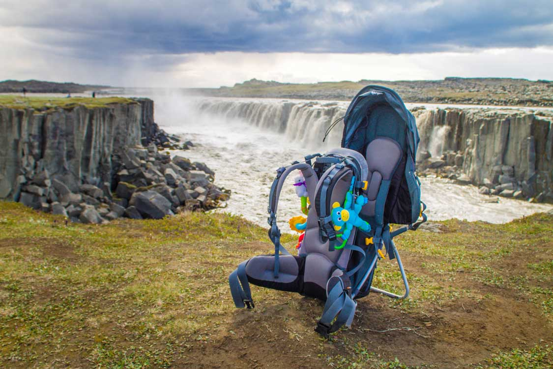 Deuter Kid Comfort child carrier on a hiking trail near a waterfall
